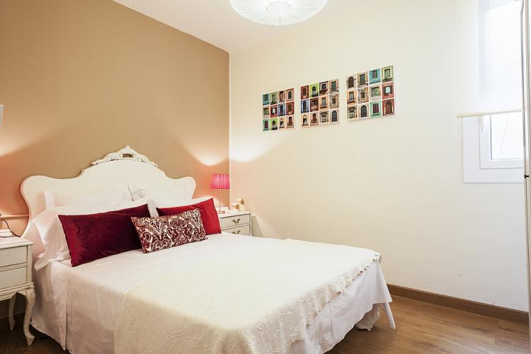The light colour bedroom with a large double bed.