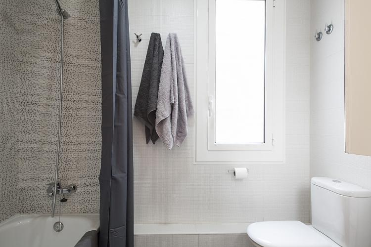 Bathroom is equipped with a bathtub, washbasin and it has a big window.