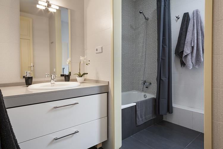 Modern stylish bathroom with a warm contrast of white and grey colors.