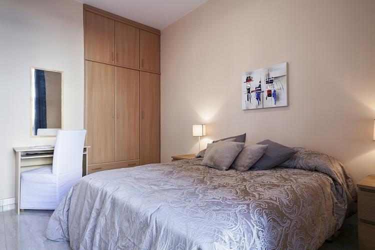 The bedroom is furnished with a large wooden armoire to maximize your storage space.