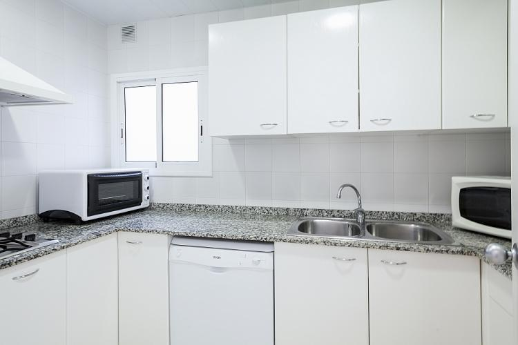 Fully equipped kitchen with bright white cabinets.