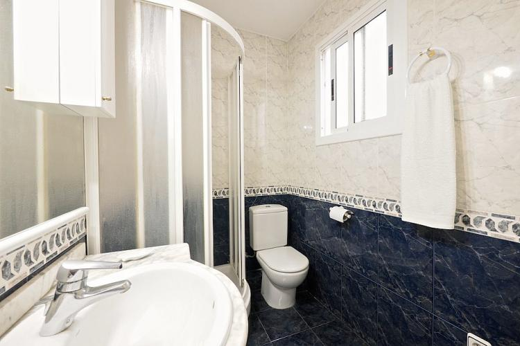 The bathroom is designed with dark grey and beige tiles