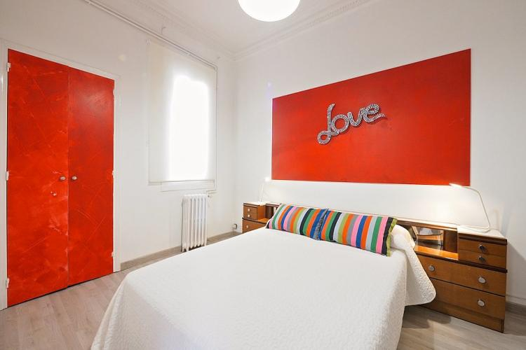 Another double bedroom, with a bright red wall decoration.