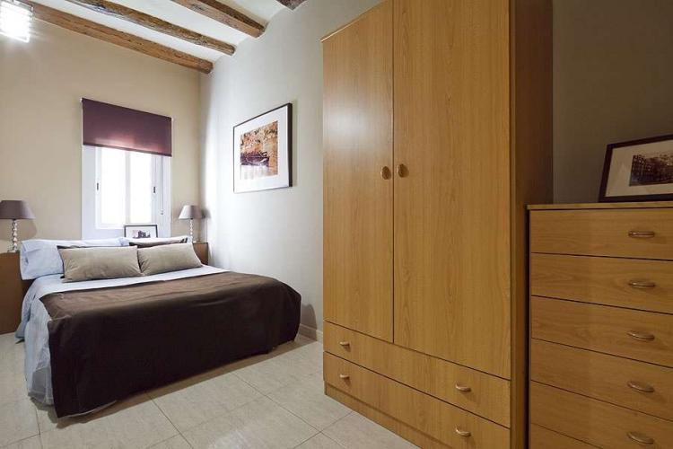 This double bedroom has a large wardrobe and a window facing the street.