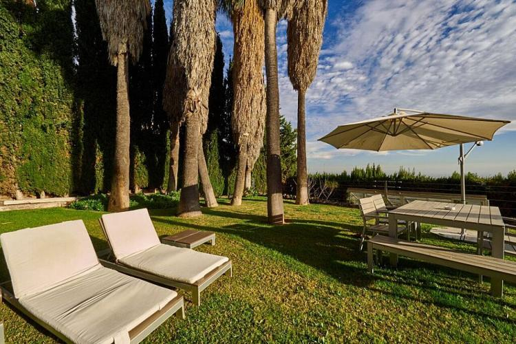 The outer grounds are furnished with cozy lounge chairs and a large table with an umbrella to protect against the harsher rays of sunshine.