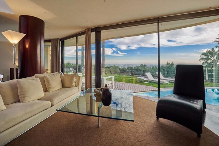 The spacious living room provides a perfect environment to lounge in with views of the pool outside.