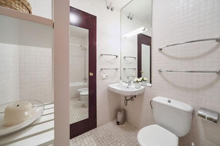 Pretty bathroom with white tiles and a faint pink touch.