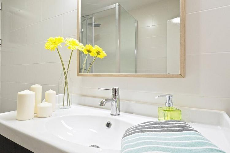 The bathroom also comes with a large, clean sink with a pretty mirror above it.