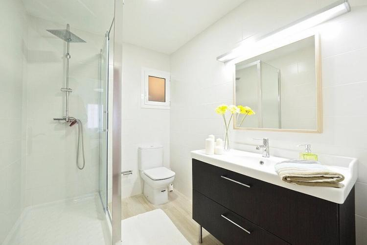 This bathroom comes with a shower accessible through elegant glass doors.