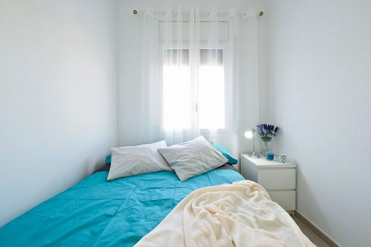 This bedroom comes with turquoise sheets, a white nightstands and armoire, and a lantern hanging above.