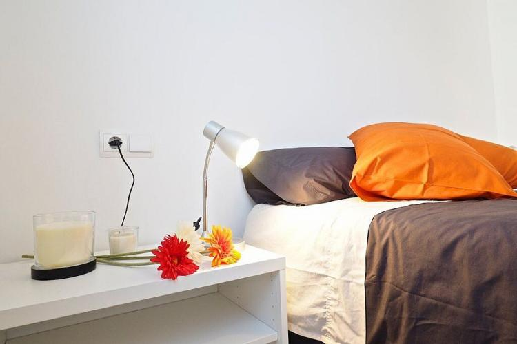A small white nightstand is the perfect place to set a reading lamp and some candles.