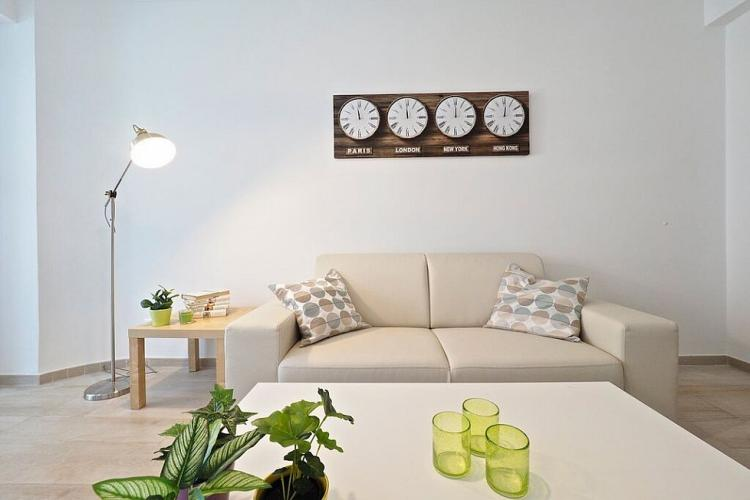 Cozy beige sofa with two matching throw pillows.