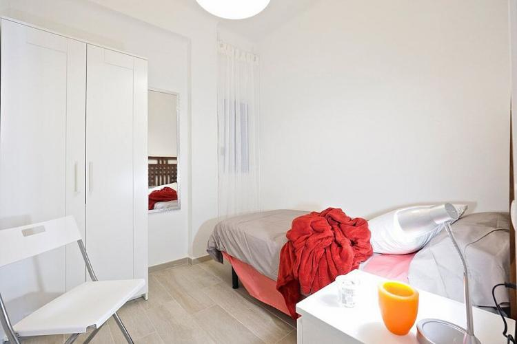 The room also comes with a large white armoire for storage and a white chair.