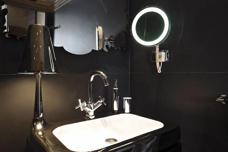The black bathroom with two elegant mirrors and lamp attached to the sink.