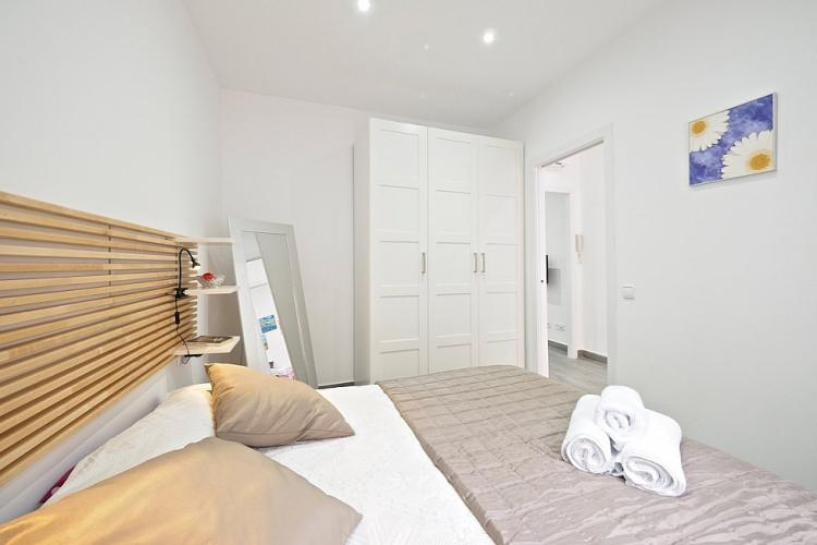 The bedroom comes furnished with a bed, a large white closet and a pretty mirror with metallic frames.