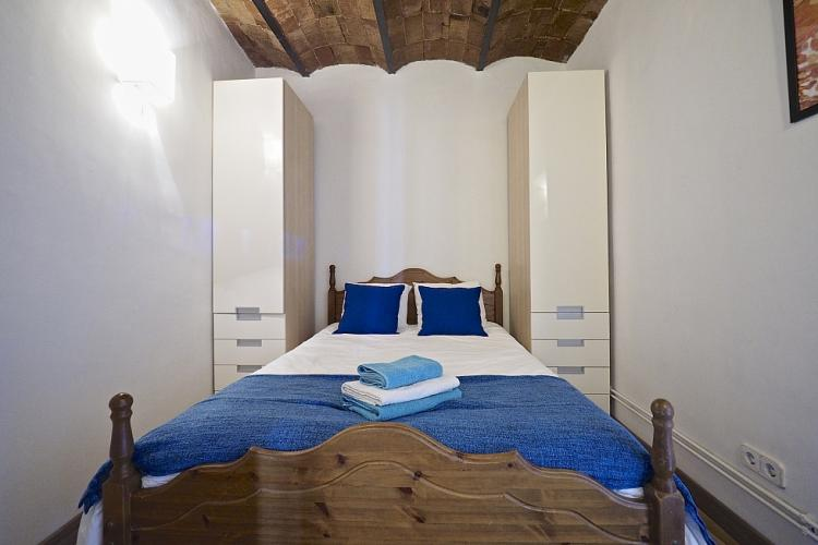 The bed is bordered on two sides by thin armoires for storage to maximize space.