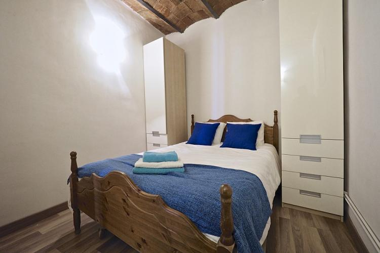 Vaulted brick ceilings and wooden furniture and floors add a relaxing ambience to this bedroom.