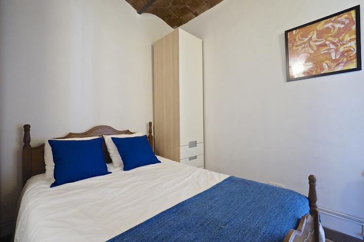 The second bedroom also comes equipped with a cozy bed in elegant wooden frames.