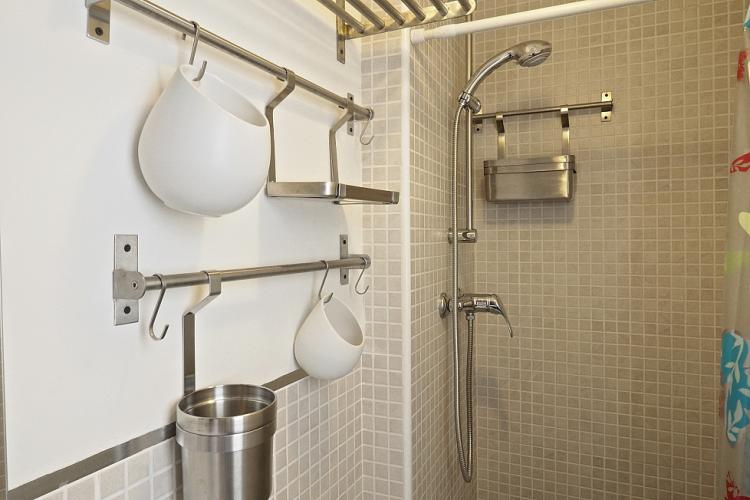 The bathroom is decked out with pretty light gray microtiles on the walls.