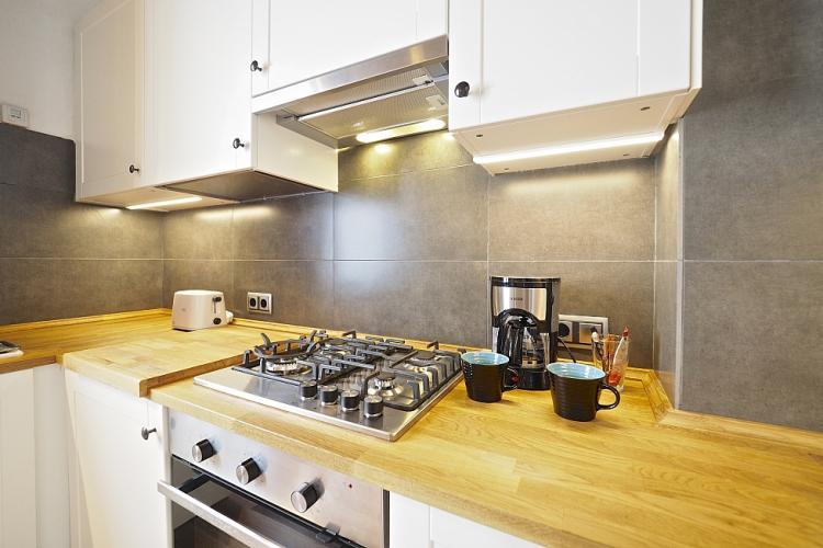 Smooth wooden counters and granite tiles on the walls of the kitchen.