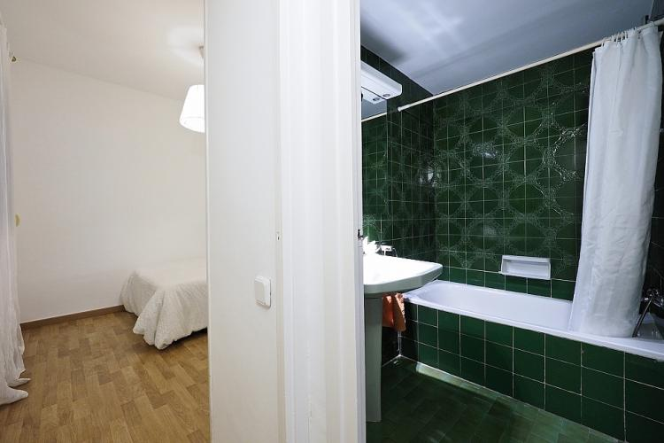 Around the corner from the bedroom you will find a divine, dark green bathroom with bathtub.