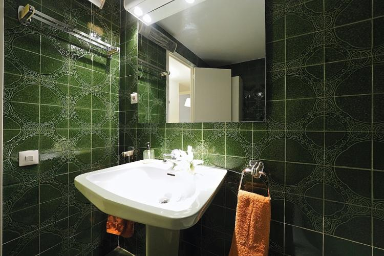 Exquisite mosaic tiles and a shiny mirror complete the unique look of this bathroom.