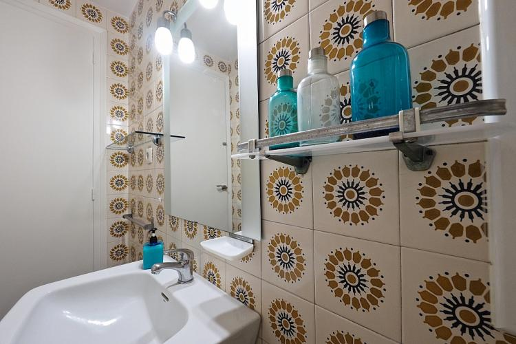 We love the contrast of the shiny mirror against the mosaic tiles, which have an antique feel.