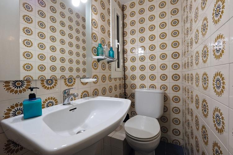 The bathroom comes with a sink and toilet, and is decorated with gorgeous mosaic tiles.