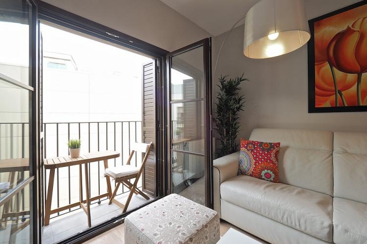 The living room also has access to a pretty balcony, furnished with a small table and chairs.