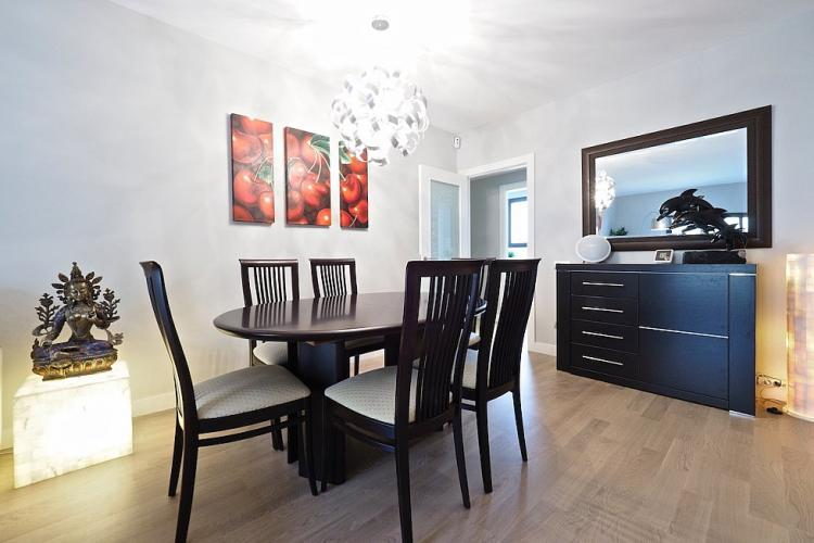 The elegant dining area comes with a black table and matching chairs for 6 and a soothing image of cherries adorning the wall.