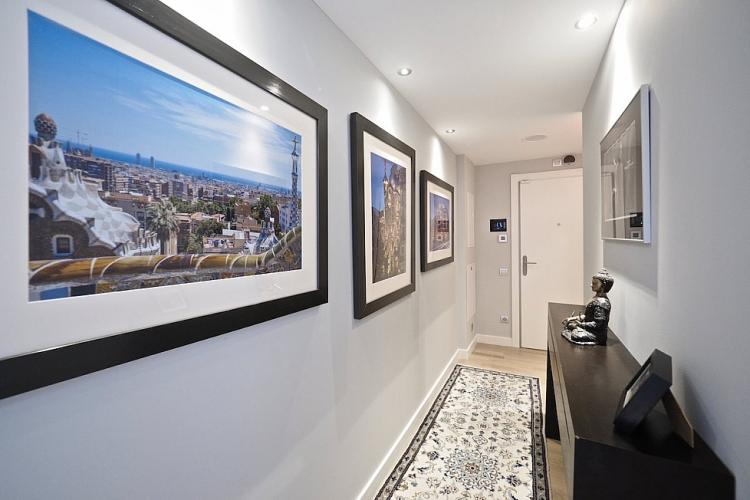 The walls of the hallway are decorated with framed images of some of the most popular sites in Barcelona.