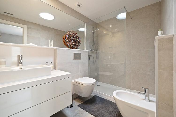 Pristine bathroom with smooth beige tiles and high quality finishes.