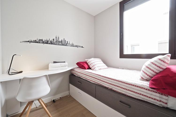 We love this adorable double bedroom with its useful design and cool stencil of the Barcelona skyline on the wall.