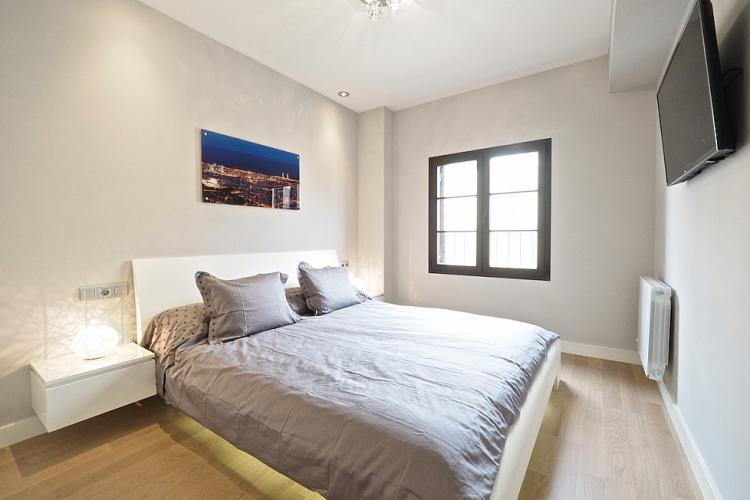 A sophisticated bedroom with smooth parquet floors and plenty of natural light.