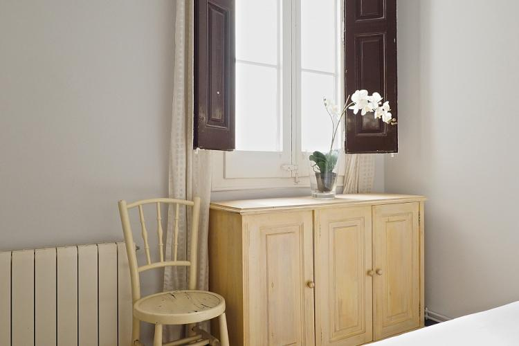 The room is also furnished with a pretty cabinet made of light wood and a chair to rest on.