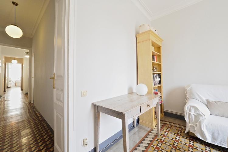Down the hall you will find a spacious living room with the same gorgeous original mosaic tiles on the floors.