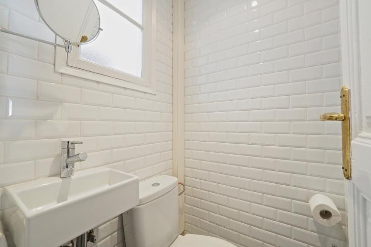 The bathroom comes decorated with bright white tiles and a white sink to match.