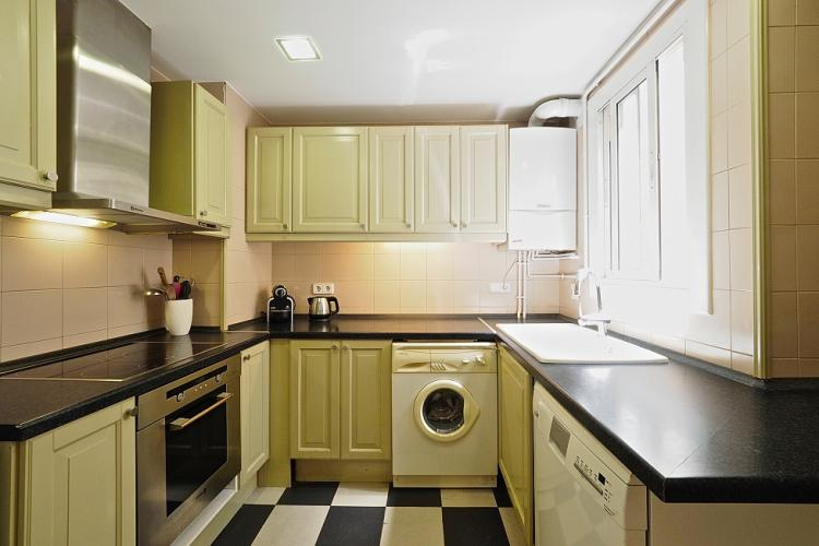 The U-shaped kitchen comes with tastefully selected light green cabinets and a black and white checkered floor.