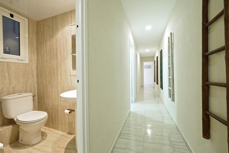 The long hallway leads to another bathroom, shared between the bedrooms.