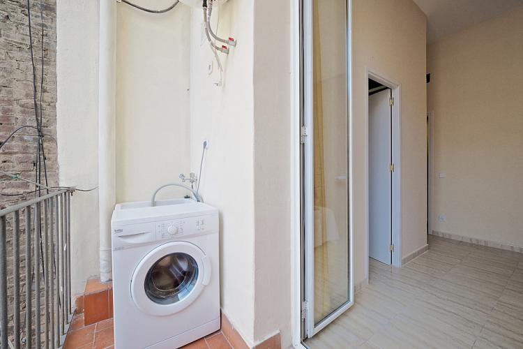 The washing machine is conveniently located on the balcony of the home.