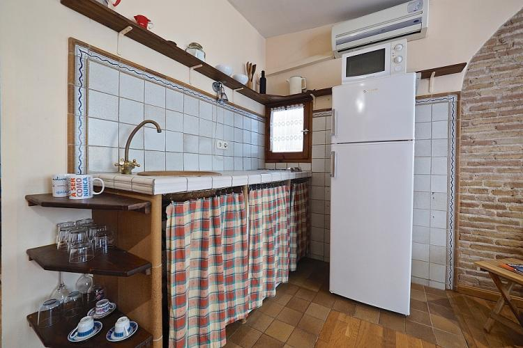 Neatly tucked kitchen in the back corner of the room