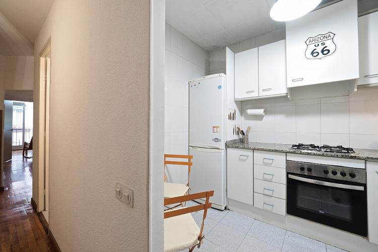 The kitchen is spacious and furnished with all-white furniture.