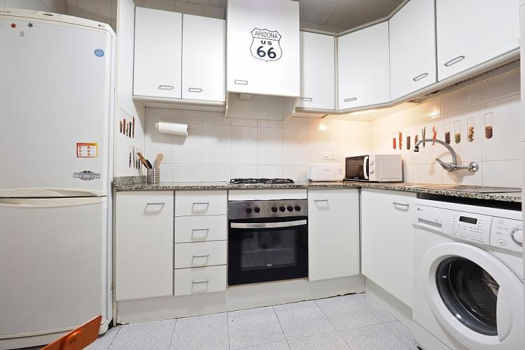 The kitchen is includes a washing machine, oven, stove, as well as other electronic utensils