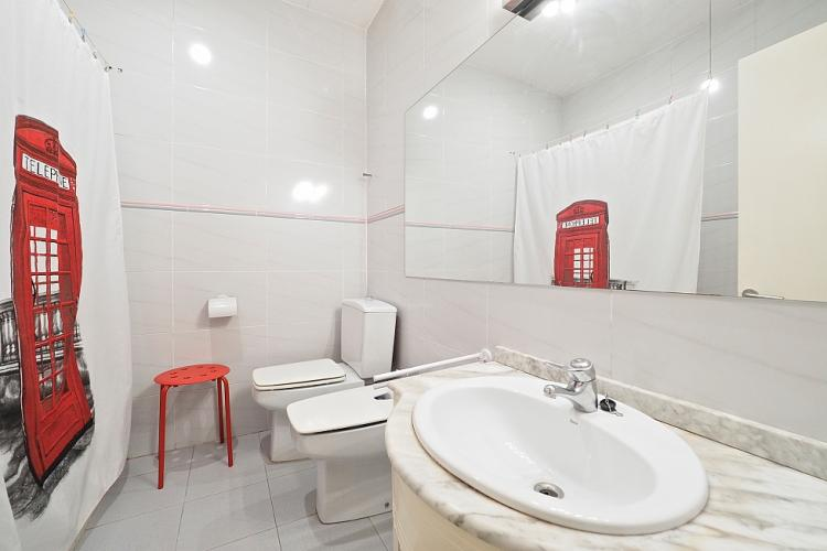 The bathroom followes a much different style compared to the rest of the apartment thanks to its red and white mix.