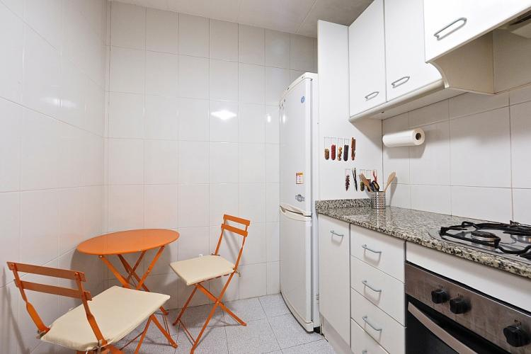 The kitchen also includes a small table with two chairs, which can be used for breakfast