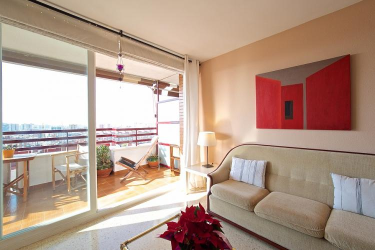 The living room has access to a spacious balcony furnished with a table and chairs.