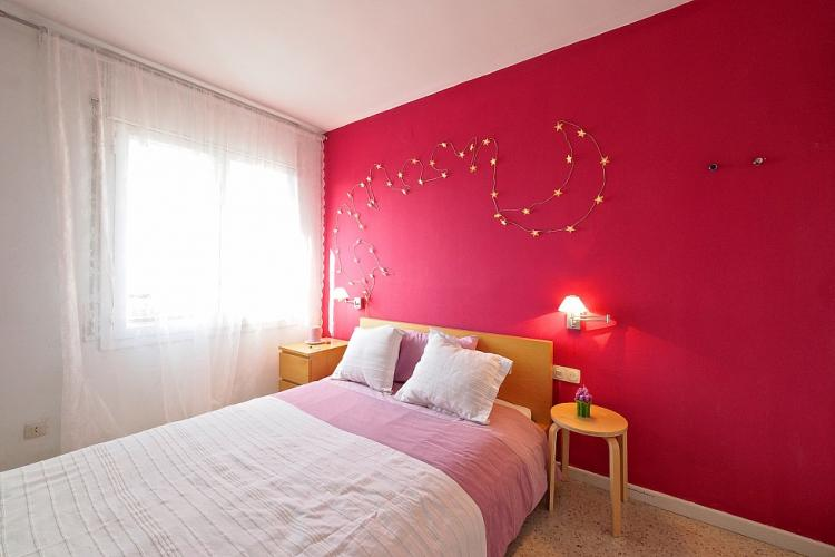Charming double bedroom with candy red back-wall and pink bedding.