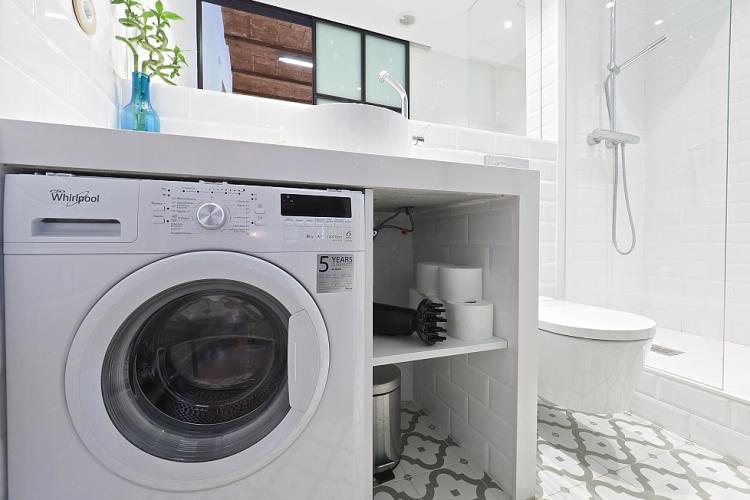 Lavadora nueva, secadora de pelo y un piso con un diseño bonito.