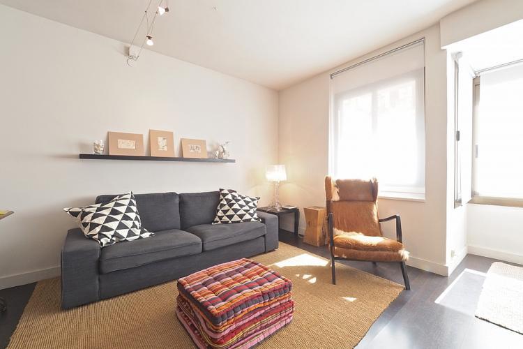 Gran sillón de estar, una silla cómoda y almohadas de piso para sentarse sobre este.
