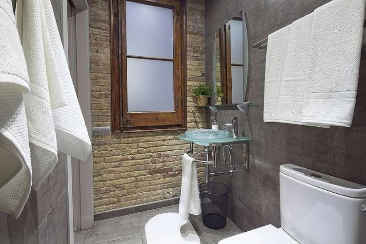 The second bathroom comes with exposed brick in the wall.
